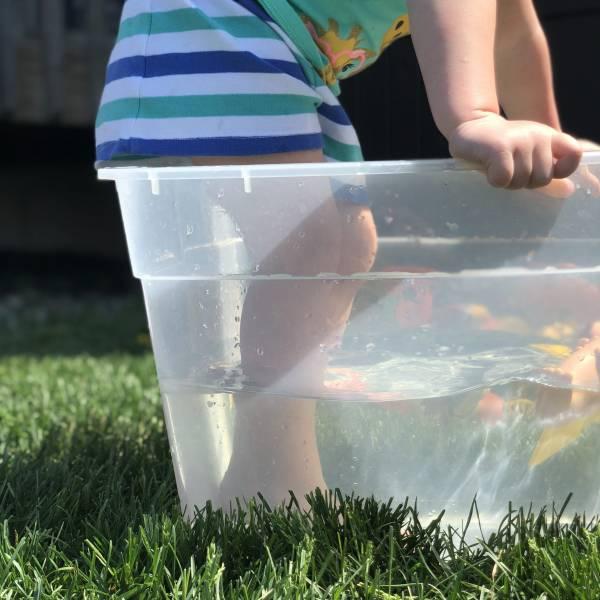 kid standing in tub of water