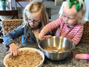 two girls making rhubarb crisp and putting pecan crumble on top