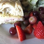 turkey pesto sandwich with fruit and salad