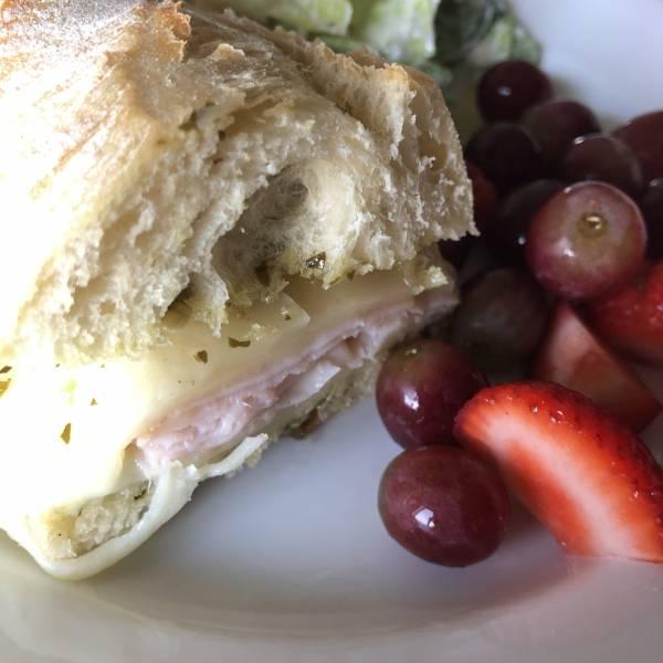 pesto turkey sandwich with fruit and salad