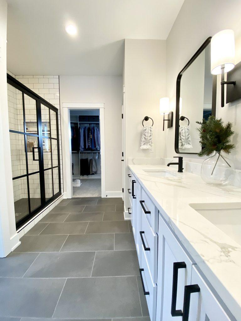black grid shower door, matte black accents, white bathroom cabinets